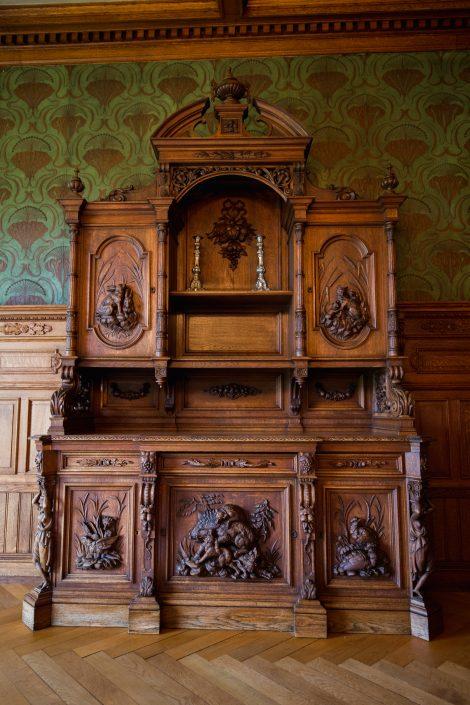 Eikeskapet er laget på stedet av to skotske møbelsnekkere. De laget brystningen og dette vakre storskapet. Jaktmotiv på skap var veldig populært for 100 år siden.
